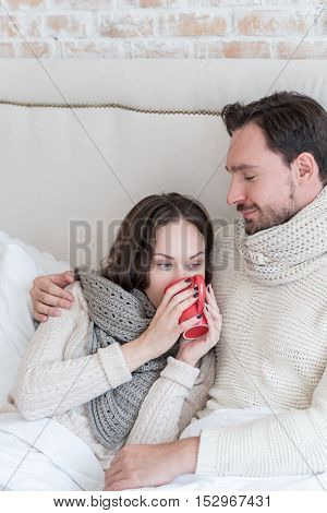 Warm feelings. Happy delighted brunette woman sitting near her boyfriend and drinking tea while leaning on him