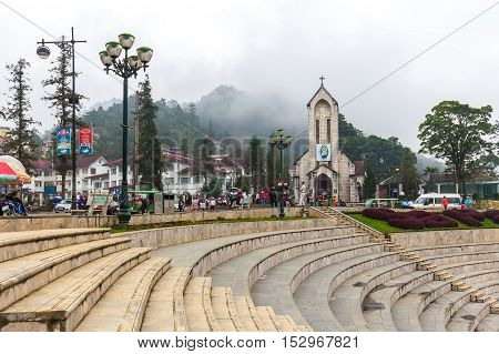 Sa Pa Vietnam - September 19 2016: Christian church inside Sa Pa near public park surrounded by amphitheater. Background is foggy mountain with cloudy sky.