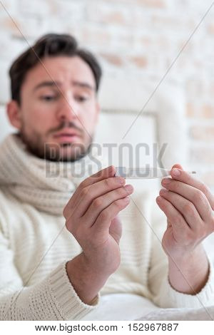 Measuring the body temperature. Selective focus of a small white body thermometer in hands of a gloomy depressed young man