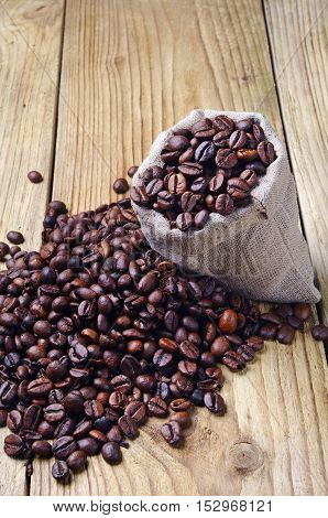 Coffee beans in a sack and spilled on the wooden table
