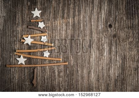 Christmas decoration, branches and stars on vintage wooden background