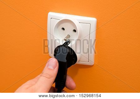 Hand Put Plug Into Electrical Socket In Wall