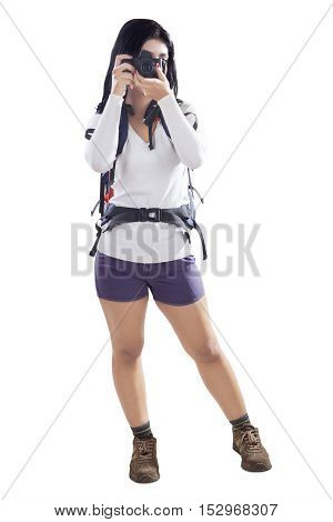 Image of a female hiker using a digital camera while carrying rucksack isolated on the white background