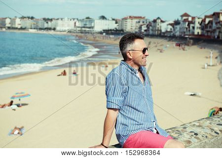 Handsome man. Outdoor male portrait. Middle-aged man resting at seafront, summer outdoor portrait, image toned.