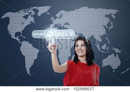 Young Asian woman pressing a virtual start button with numbers 2017 and world map on the futuristic screen