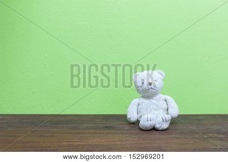 teddy bear on old wood and green wall background