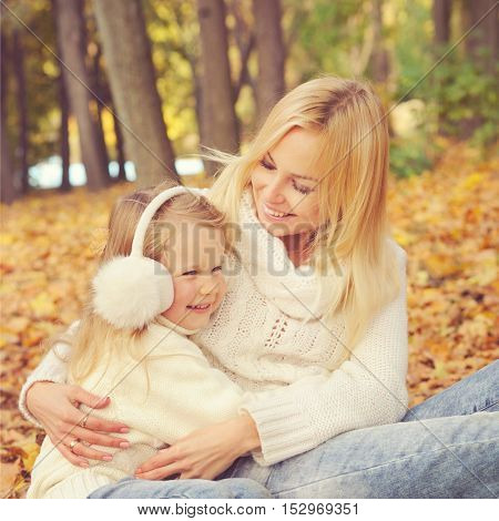 Happy family in park, smiling mother and little daughter take a rest in autumn park