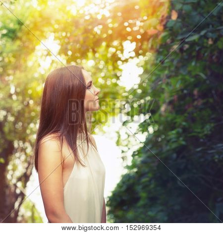 Portrait of a young woman lighten rays of sunlight, standing on a forest way