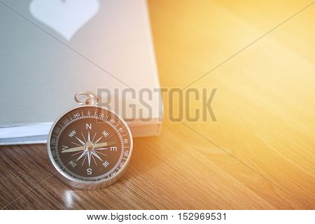 Compass over the book on wooden table with light flare and copy space