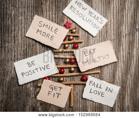 Christmas Tree And New Year Resolutions On Rustic Wooden Background