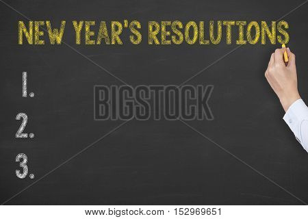 Human Hand Writing New Year Resoulutions on Chalkboard Background