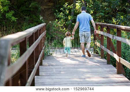 Dad with his little daughter down wooden stairs in park