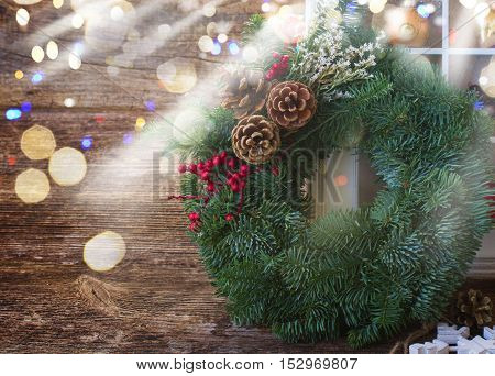 pine evergreen wreath with bokeh glimming lights