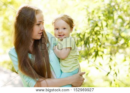 Young mother hugging little girl in summer park