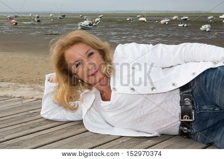 Mature And Blond Woman Laying On The Wooden Jetty