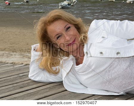 Senior Blond Woman Laying On The Wooden Jetty