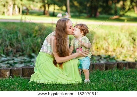 Mother kisses daughter in summer park on green lawn