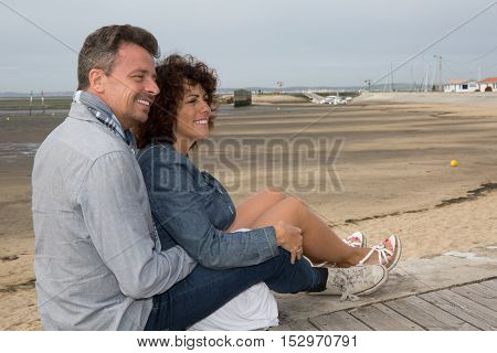 Cheerful Middle Aged Couple Sitting On The Wooden Jetty