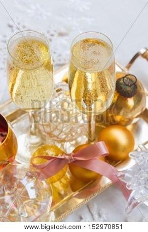 Two glasses of christmas champagne with bubbles and christmas golden decorations