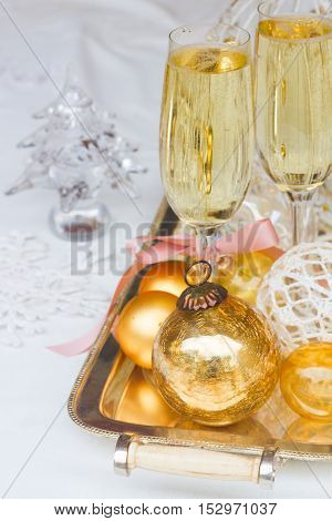 Two glasses of christmas champagne with bubbles and christmas gold decorations