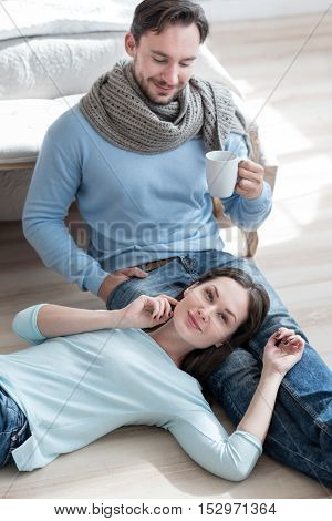 Enjoying time together. Good looking cheerful young man holding a tea cup and looking at his girlfriend while sitting in the bedroom