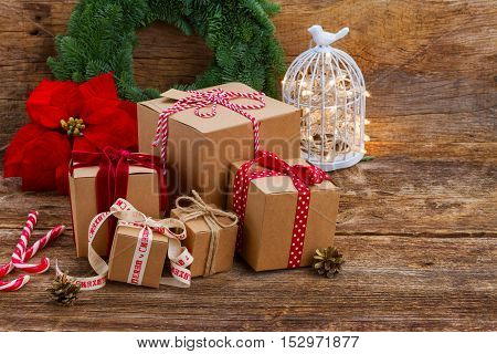 Carton handmade gift boxes on wooden background, poinsetia or christmas red star flower in background