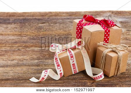 three handmade gift boxes on wooden table isolated on white background