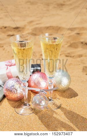Two glasses of christmas champagne and bubbles with christmas gifts and decorations on beach
