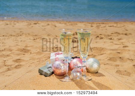 Two glasses of christmas champagne and bubbles with christmas gift boxes and decorations on beach by the tropical sea