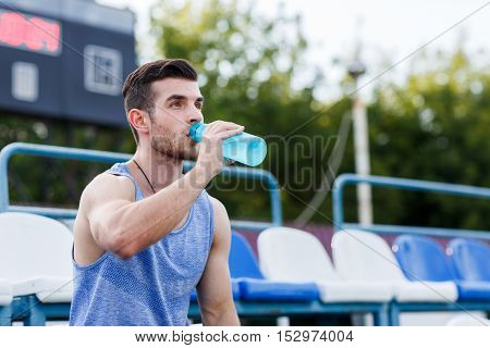 Handsome athletic man drinking water at sports stadium after training om summer day