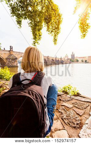 Female traveler enjoys views of the Charles Bridge in Prague. Czech Republic. Charles Bridge with its statuette, Old Town Bridge Tower, St. Francis Of Assissi Church in the background.