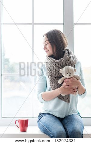 Sitting on a windowsill. Pleasant cute young woman holding a teddy bear and smiling while turning her head