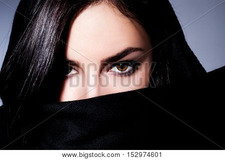 beautiful black hair woman with black scarf over her face studio closeup