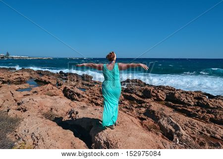 middle-aged woman on the beach. middle-aged woman in a dress enjoying the warm sea breeze and stunning views of the ocean