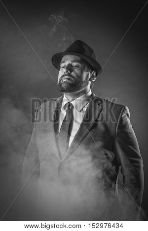 Businessman on a suit smoke black background