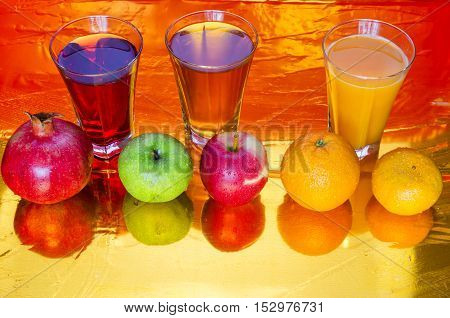 freshly squeezed juices from the red apples, tangerine and pomegranate on a red background