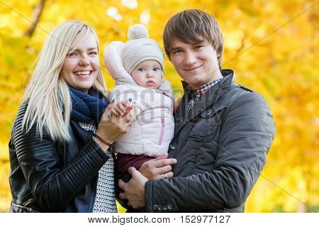 Young family with little daughter on hand in autumn park