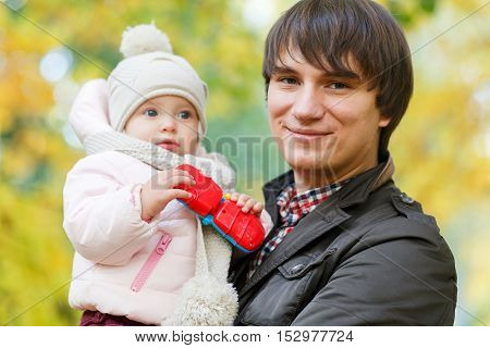Happy dad holding baby with toy in hands on background of autumn landscape
