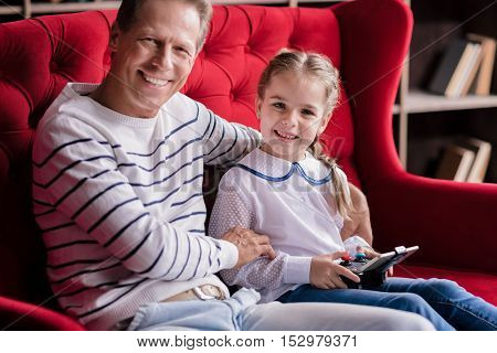 Time for playing games. Delighted girl sitting on the couch with her grandfather and holding the game console while resting together
