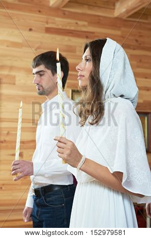 Orthodox wedding ceremony. man and woman with candles at church