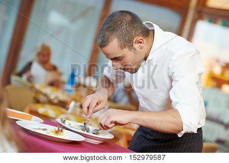 waiter man dressing fish at restaurant