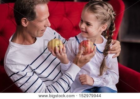 Look what I have. Cute little girl sitting on the couch and holding two apples while resting with her grandfather