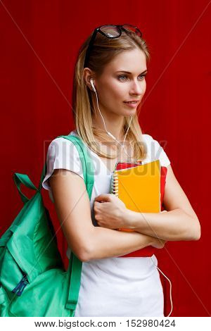 Student in headphones and with Tablet stand near red wall