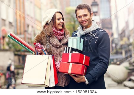Picture showing young couple doing Christmas shopping in the city