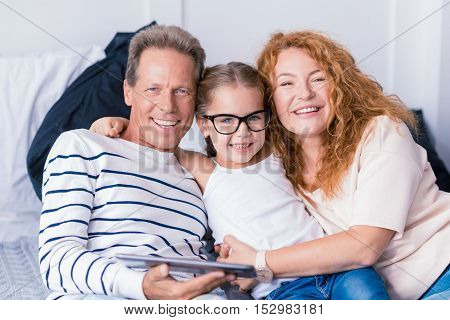 I love my grandparents. Smiling little girl sitting on the bed with her grandparents and hugging them while having fun at home