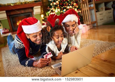Smiling family lying on floor front of Christmas tree and looking at laptop