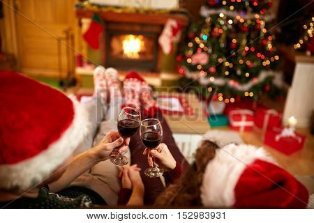 Couple toasting with glasses of red wine for Christmas, back view