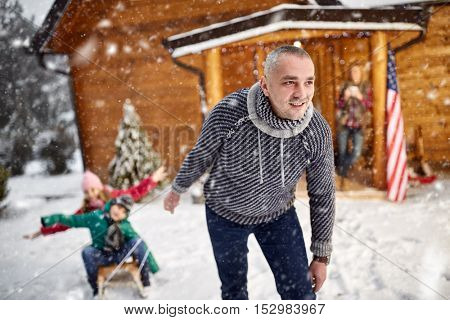 winter holidays and family concept - happy family with child on sled in winter outdoor
