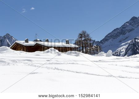 Mountain Cabin Submerged By Snow On A Sunny Day