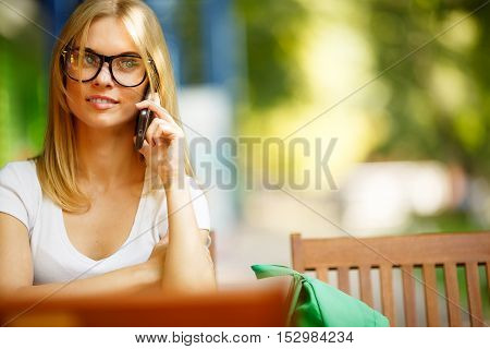 Student with phone on background of green trees, blurred background